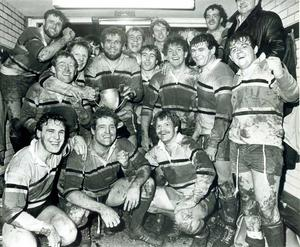 """We've won the cup! Jubilant Bangor players surround their skipper David Morrow in the Upritchard Park dressing room following their Bass Boston Cup triumph over Instonians last night. Bangor, who host the tournament, have now won the trophy  five times since the competition was inaugurated in 1974. Bangor are the current holders of the senior league title and are now lining up a possible Ulster """"Grand Slam."""" 21/12/1983"""