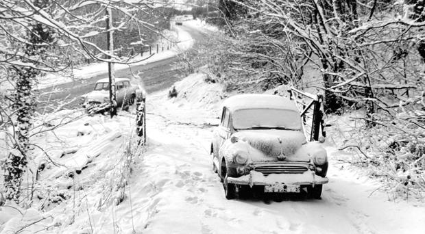 A Morris Minor freezed over after it was abandoned by its driver on a steep, snow-covered hill on the outskirts of Belfast many winters ago