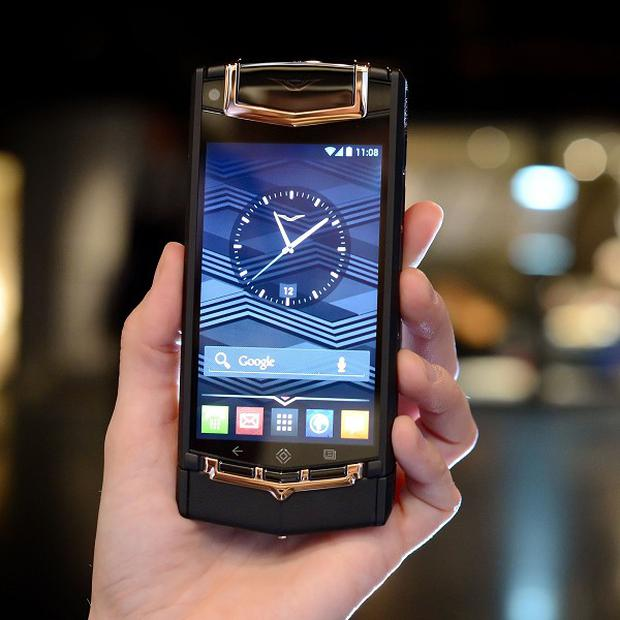 A woman holds a Black PVD Titanium Red Gold and Mixed Metals Vertu Ti smartphone, which retails for £14,200 (16,500), at its launch at the London Film Museum, in central London. PRESS ASSOCIATION Photo. Picture date: Tuesday February 12, 2013. It is the latest high-end phone by the British company, formerly part of Nokia until it was sold to private equity outfit EQT last year. It hit the headlines in 2002 offering a £15,000 Nokia phone available in 18-carat gold, white gold and top-of-the-range platinum cases. See PA story TECHNOLOGY Mobile. Photo credit should read: Dominic Lipinski/PA Wire