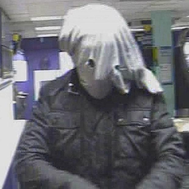 A knife-wielding robber described as 'looking like the elephant man' during a raid on a betting shop (West Midlands Police/PA)