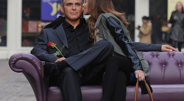 A member of the public sits next to a Madame Tussauds' waxwork figure of actor George Clooney in London's Carnaby Street