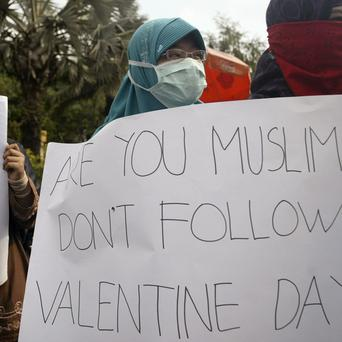 Muslim students hold posters during a protest against Valentine's Day in Surabaya, Indonesia (AP)