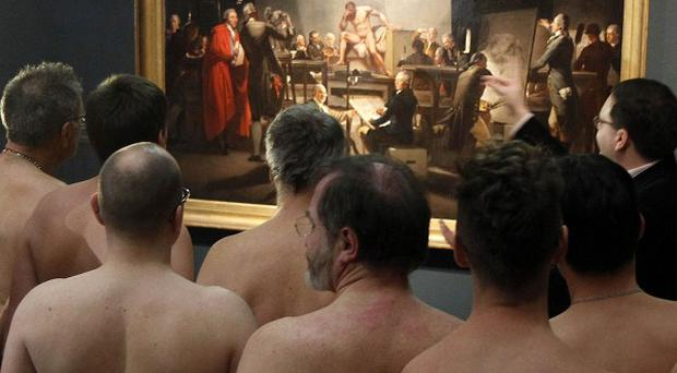 Naked museum visitors look at pictures of the show Nude Men from 1800 to Today during a special opening at the Leopold Museum, Vienna (AP)