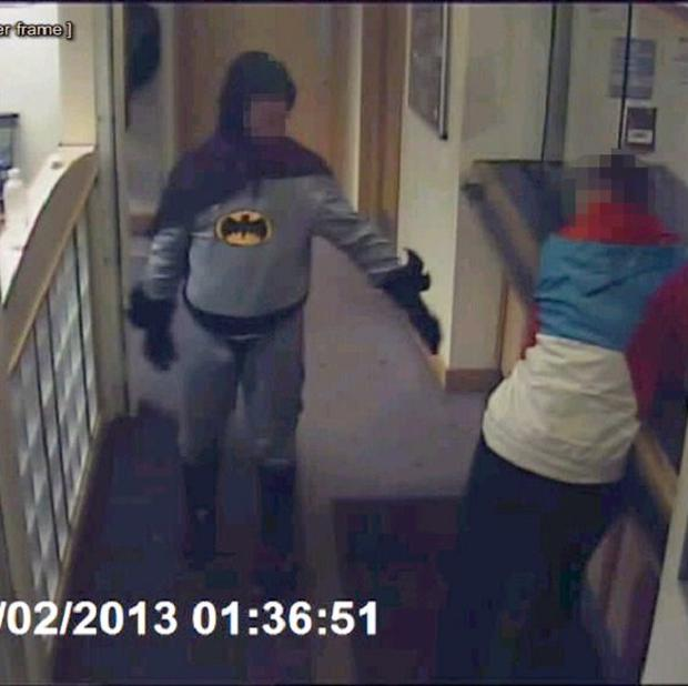 A man dressed as Batman hands over a suspect at Trafalgar House police station in Bradford