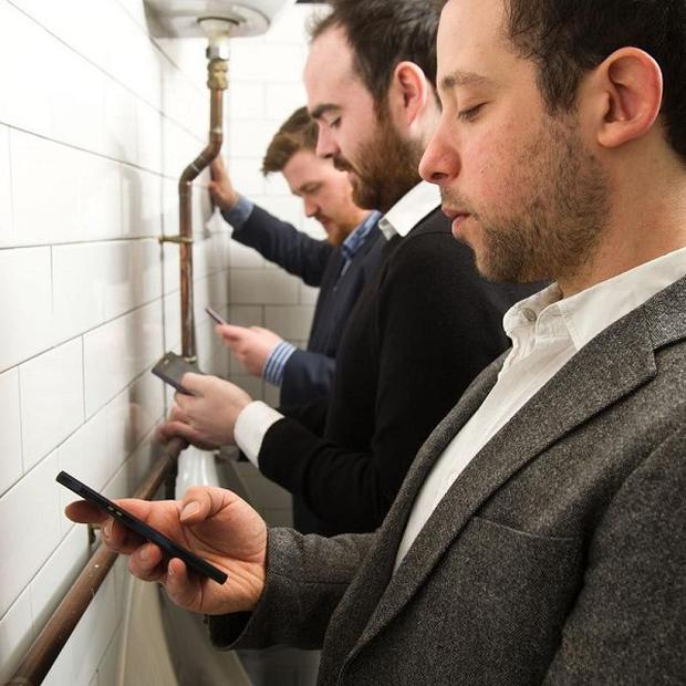 A quarter of men admit to sitting down on the toilet to urinate so they are 'hands free' to continue using their mobile phone, a survey claims