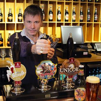 Iron Maiden lead singer Bruce Dickinson pulls a pint of real ale Trooper