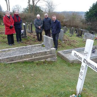 MP Simon Hart, right, and members of St Martin's Church in Laugharne look at damage caused by badgers near Dylan Thomas's grave