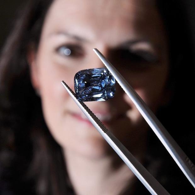A female employee of Bonham's Auctioneers in central London studies the rare deep-blue diamond ring