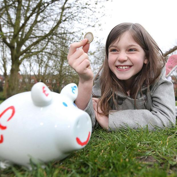 Aisling Kavanagh, eight, poses with a piggy bank to highlight new research revealing many children have already started saving