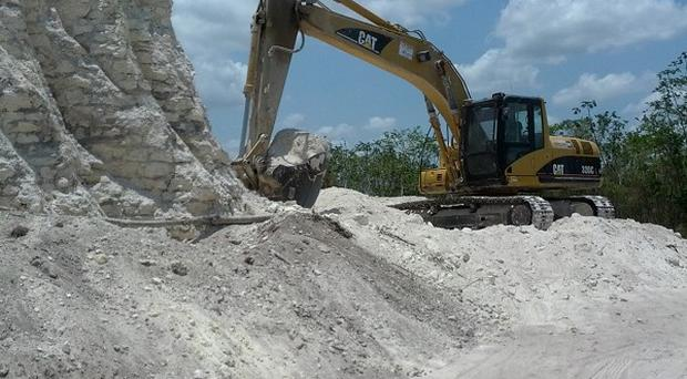 A backhoe claws away at the sloping sides of the Nohmul complex, one of Belize's largest Mayan pyramids (AP)