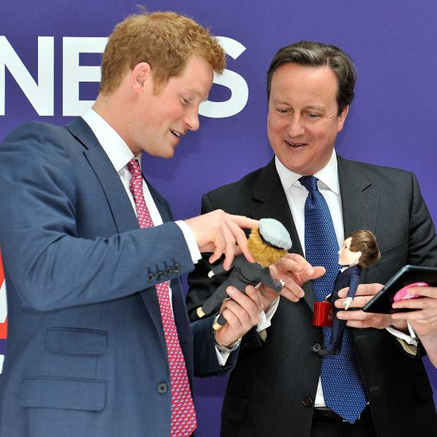 Prince Harry and David Cameron are presented with dolls during their visit to New York