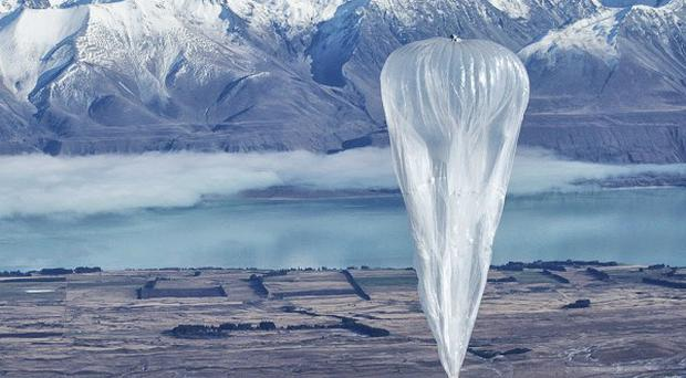 A Google balloon sails through the air with the Southern Alps in the background, in Tekapo, New Zealand (AP/Jon Shenk)