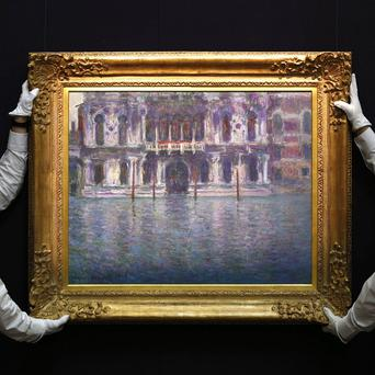 Sotheby's employees pose with the 1908 painting Le Palais Contarini by Claude Monet (AP/Sang Tan)