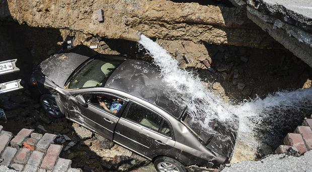 A car at the bottom of a sinkhole caused by a broken water main in Toledo, Ohio (AP/Toledo, Ohio Fire and Rescue Department, Lt Matthew Hertzfeld)