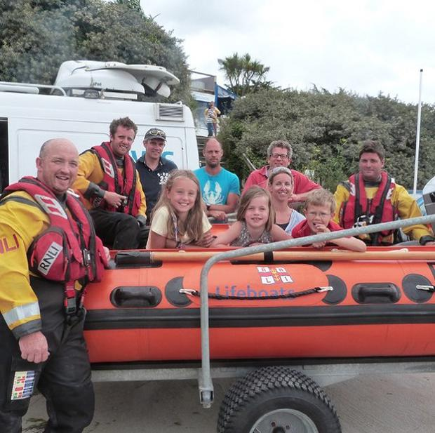 A family rescued after writing a message for help in the sand have thanked an RNLI crew
