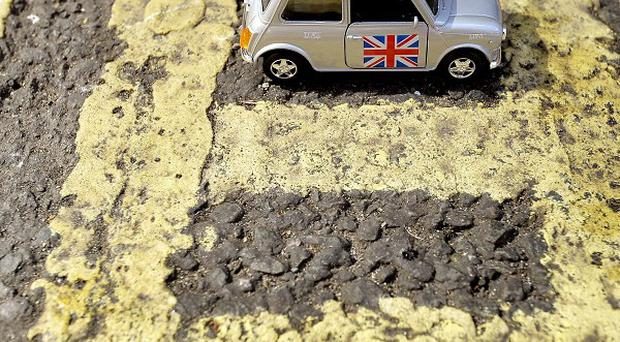 A toy car illustrates what could be the smallest double yellow lines restricted parking space in the UK, in Caxton Street, Westminster.