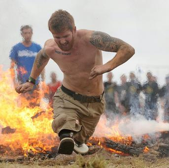 Double amputee James Simpson tackles the fire obstacle during the Spartan Super Race