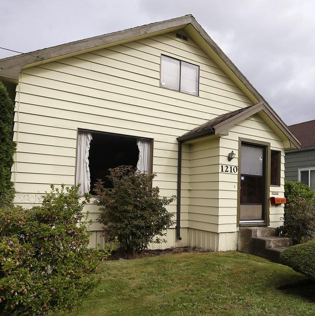 The childhood home of Kurt Cobain, the late frontman of Nirvana, left, along an alley in Aberdeen, Washington.