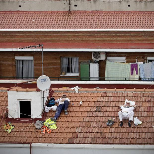Workers take a nap on a roof in Madrid, Spain (AP)