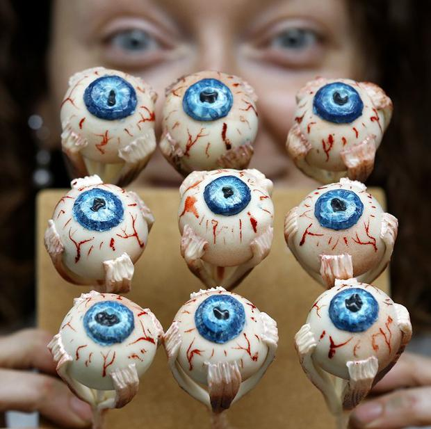 Cake Artist Sarah King displays her eyeball cakes at the Feed the Beast extreme cake shop in London (AP)