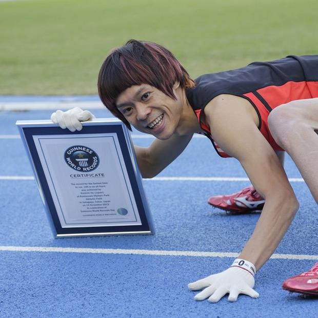 Kenichi Ito poses with a Certificate of the Guinness World Records after setting the fastest time for the 100-metre dash on his arms and legs (AP)