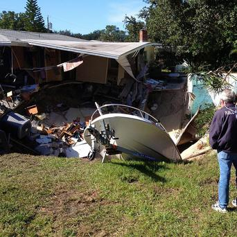 A man observes a sinkhole which has swallowed parts of two houses in Dunedin, Florida (AP/The Tampa Tribune, Luke Johnson)