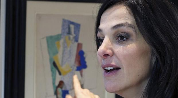 French TV producer Peri Cochin in front of Picasso's 1914 cubist drawing Man with Opera Hat, at Sotheby's auction house in Paris (AP)