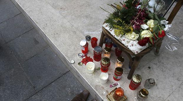 Flowers and candles decorate a wooden chair with a photo of late Husein Hasani, in downtown Sarajevo (AP)