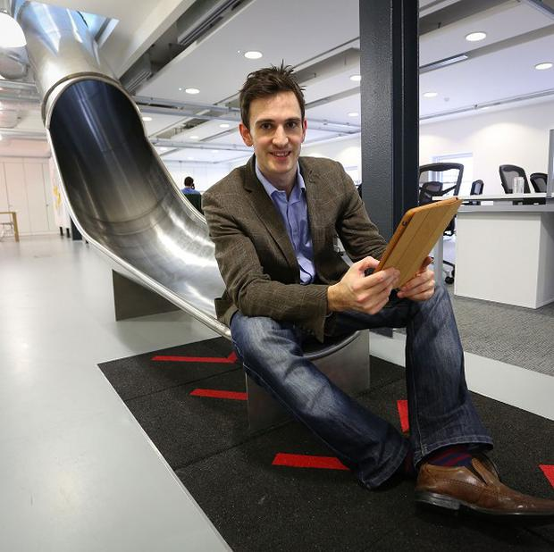 James Avery, manager at the Works in Folkestone, Kent, an innovative business hub, checks his tablet computer as he travels between the floors of his office using a slide installed for staff last summer (PA)