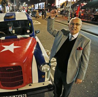 London taxi driver Tony Caccavone and his cab, painted in the colours of the Cuban flag (AP)