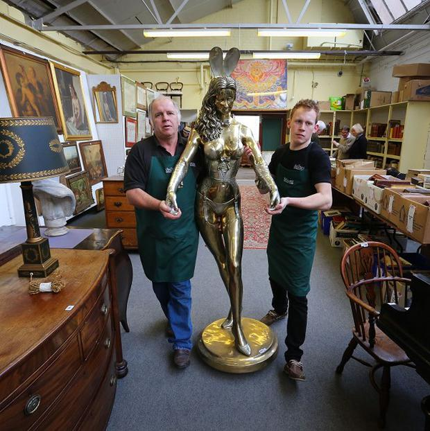 Porters at Bellmans Auctioneers carry the gilt bronze Playboy Bunny Girl Waitress by sculptor Rudolfo Bucacio into the sale room