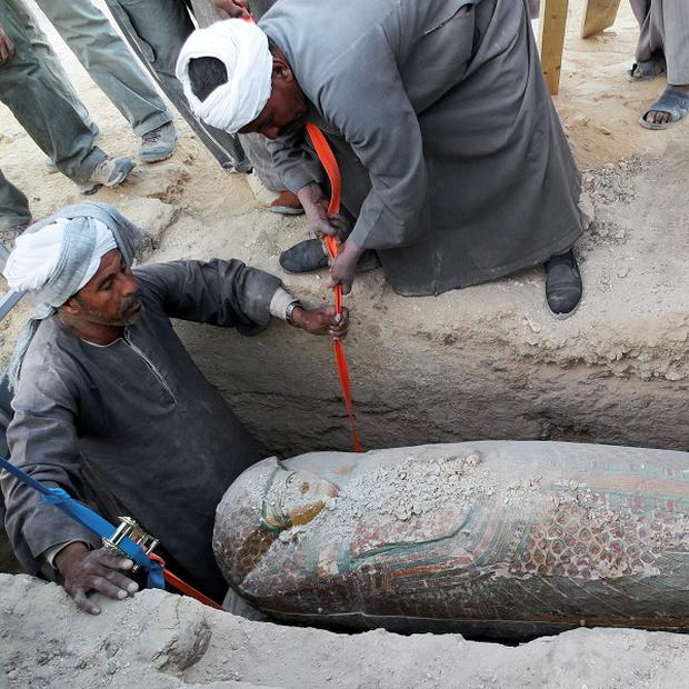 Egyptian men dig up a preserved wooden sarcophagus that dates back to 1600 BC, when the Pharaonic 17th Dynasty reigned, in Luxor, Egypt (AP/Egypt's Supreme Council Of Antiquities)