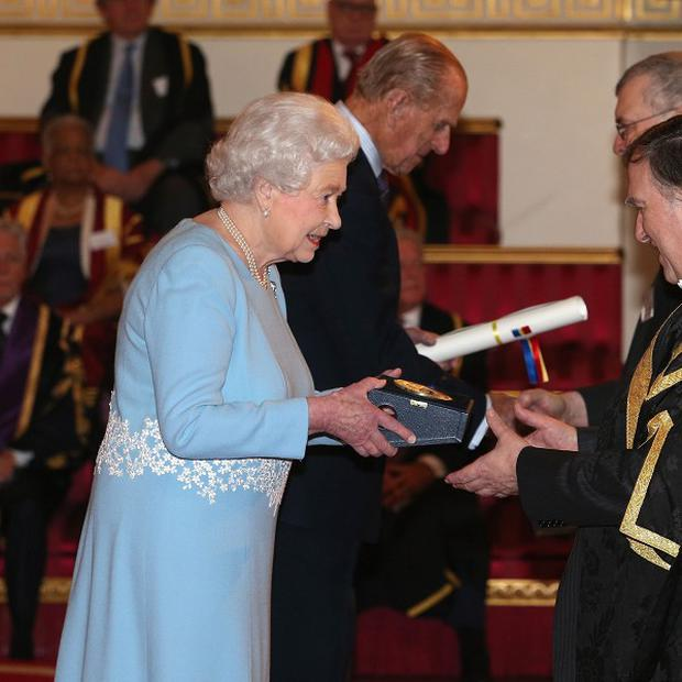 The Queen presents a Queen's Anniversary Prize for Higher and Further Education Award to Sir Robert Burgess of the University of Leicester.