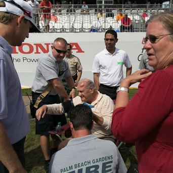Spectator Edwin Curtis, centre, receives attention after being hit by a ball during the Honda Classic (AP)