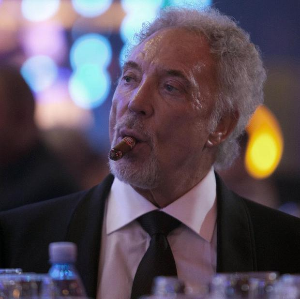Tom Jones smokes a cigar during a gala dinner marking the end of the 16th annual Cigar Festival in Havana, Cuba. (AP)