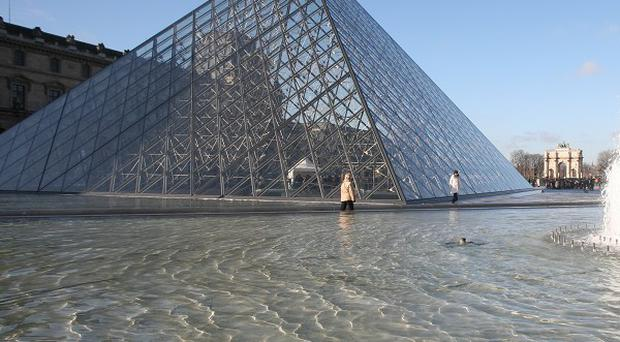 Police in Paris said they arrested six women for baring their breasts outside the pyramid-shaped entrance to the Louvre.