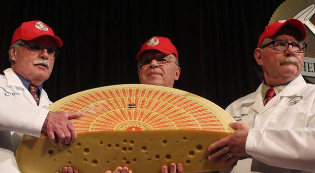 Three judges for the 2014 World Championship Cheese Contest hold the champion, a Swiss Emmentaler (AP)