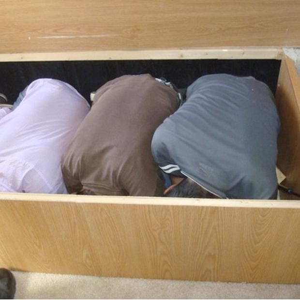 Three adult Mexican immigrants were found crouched in a box under a recreational vehicle near San Diego (US Department of Homeland Security/AP)