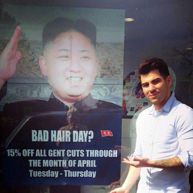 Barber Karim Nabbach standing next to a poster poking fun at North Korean leader Kim Jong-un's unusual hairstyle