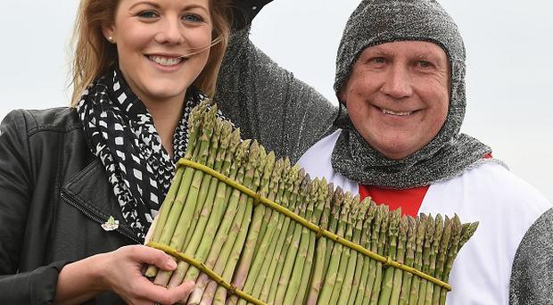 Katie Sexton, 20, celebrates the start of the asparagus season with St George and a round of asparagus spears in Worcestershire.
