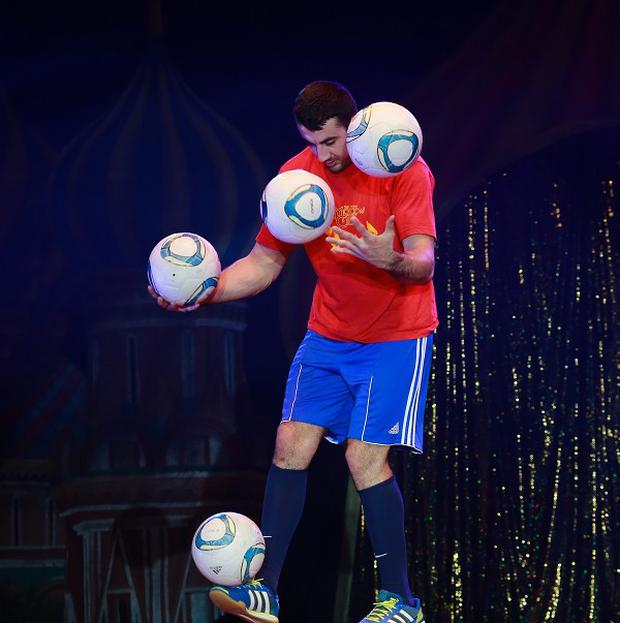 Zhora Oganisyan, a football juggler from The Moscow State Circus, on his way to breaking his own record of balancing on a giant football whilst juggling footballs