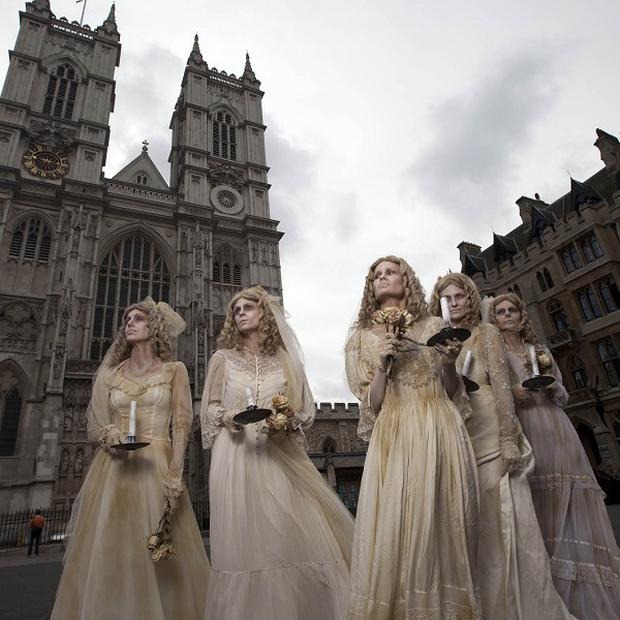 A group of five actresses dressed as the Charles Dickens character Miss Havisham, outside Westminster Abbey