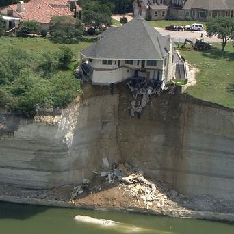 The owner of a house teetering on a crumbling cliff over a Texas lake has decided to burn it (AP/WFAA.Com)