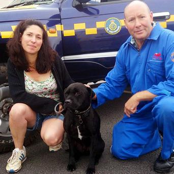 John Bunce, a member of the Torbay Coastguard rescue team with Harry, a Staffordshire bull terrier cross breed dog, who has been reunited with his owner Amanda Wileman after he went missing for more than 12 hours (PA/HM Coastguard)