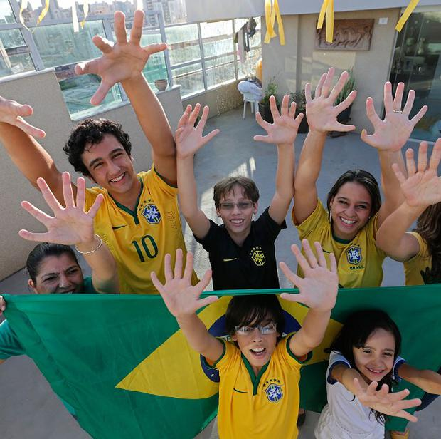 Members of the Silva family show that they each have six fingers on their hands in Brasilia, Brazil (AP)