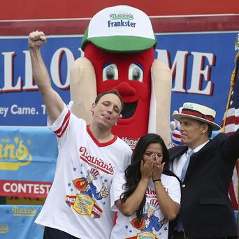Joey Chestnut celebrates after successfully proposing to his girlfriend and fellow competitor Neslie Ricasa (AP)