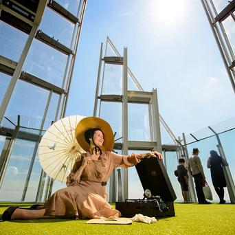 Maureen Schipper sits on the new artificial lawn on the observation deck at the top of the Shard, in central London, which has been installed as part of the the View From the Shard's summer season of events