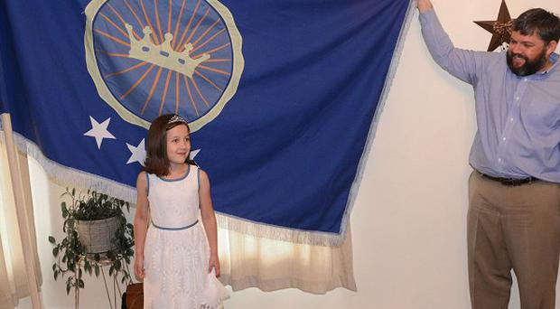Jeremiah Heaton and his seven-year-old daughter, Princess Emily, with their flag representing the Kingdom of North Sudan (AP/Bristol Herald Courier)