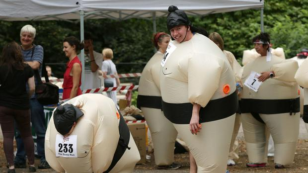 Participants warm up before taking part in the Sumo Run in Battersea Park, London