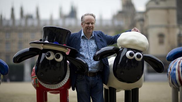 Nick Park poses with sculptures of Shaun the Sheep (AP)